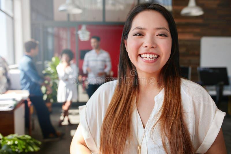 Gladlynt ung asiatisk kvinna som i regeringsställning står royaltyfria foton