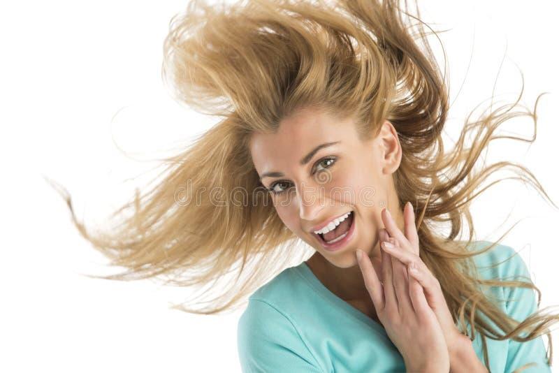 Gladlynt ung blond kvinna som kastar hår royaltyfria bilder