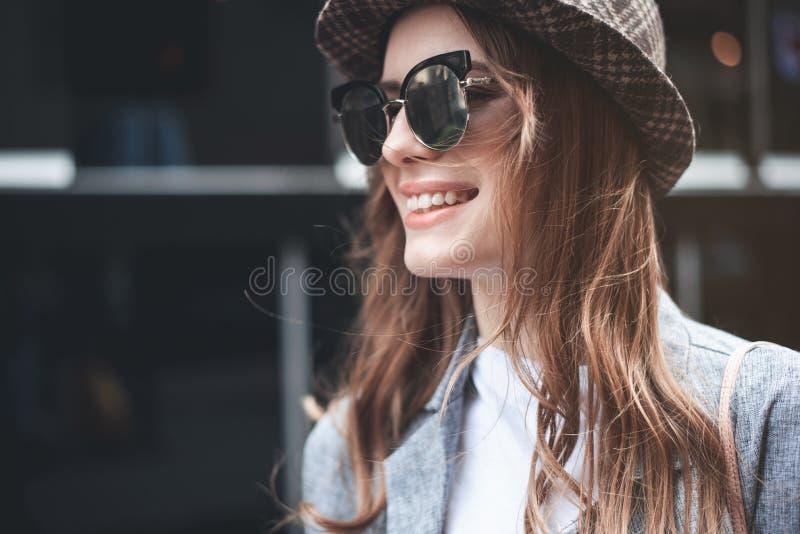 Gladlynt ung dam i moderiktig hatt och mörkt glasögon arkivbild