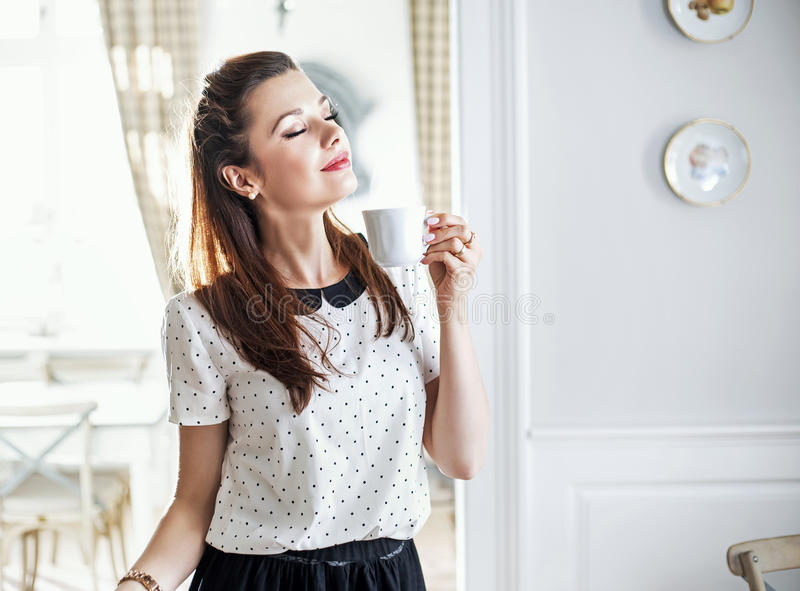 Gladlynt ung dam som dricker morgonkaffe royaltyfria foton
