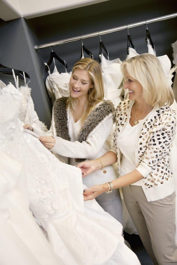 Gladlynt ung dotter med den höga modern som väljer bröllopsklänningen i brud- boutique arkivbild
