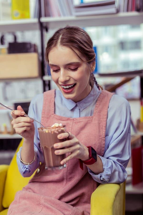 Gladlynt ung flicka som fångar mini- marshmallower från kakaoexponeringsglas royaltyfria foton