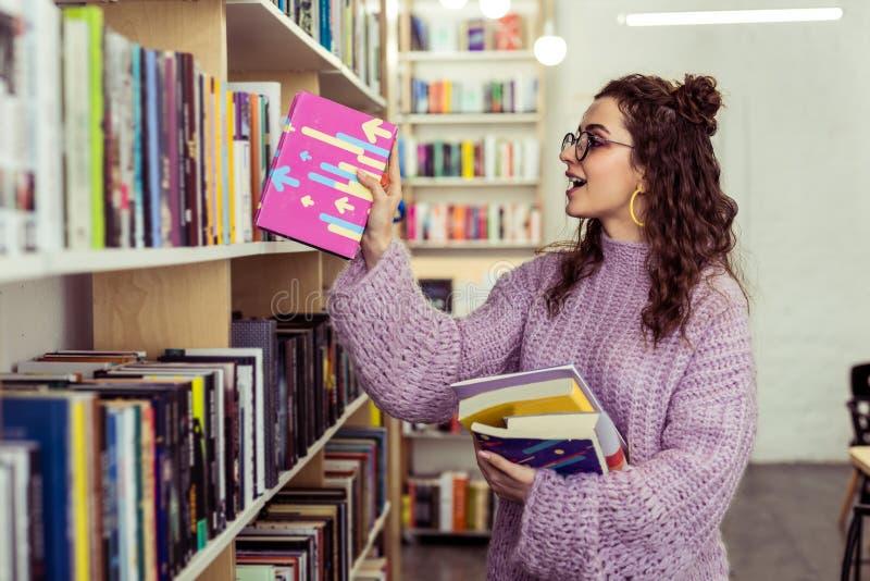 Gladlynt ung flicka som sätter ner den lästa rosa boken arkivfoton