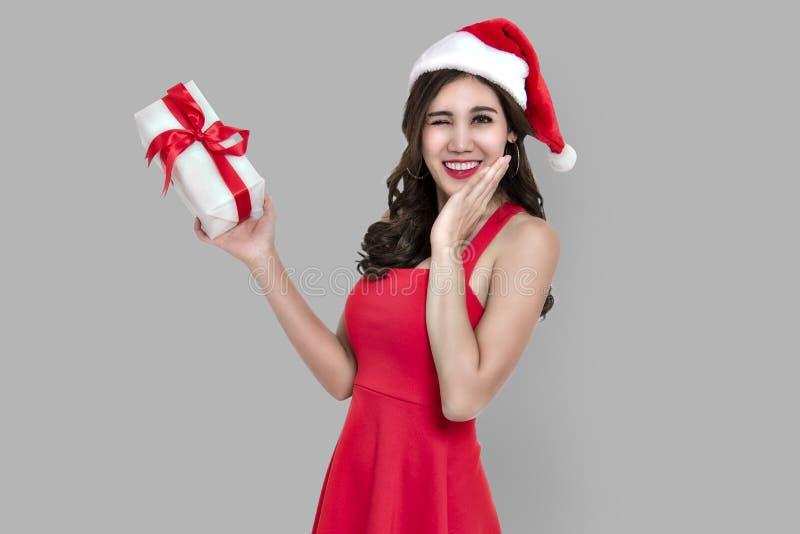 Gladlynt ung kvinna i för santa för röd klänning ask hållande gåva fotografering för bildbyråer