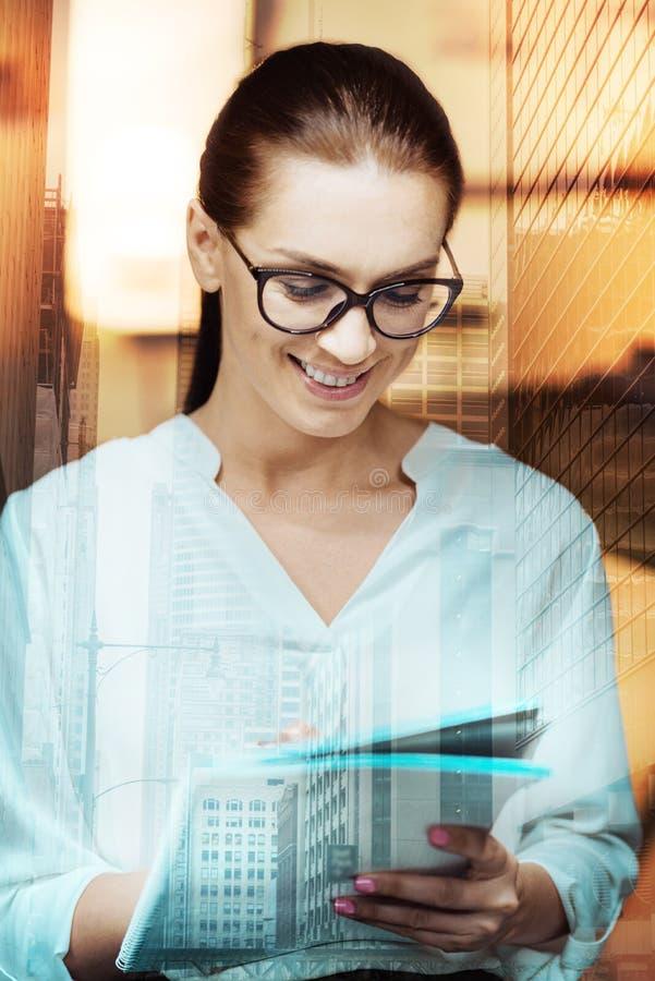 Gladlynt ung kvinna i glasögon genom att använda minnestavlan arkivbilder