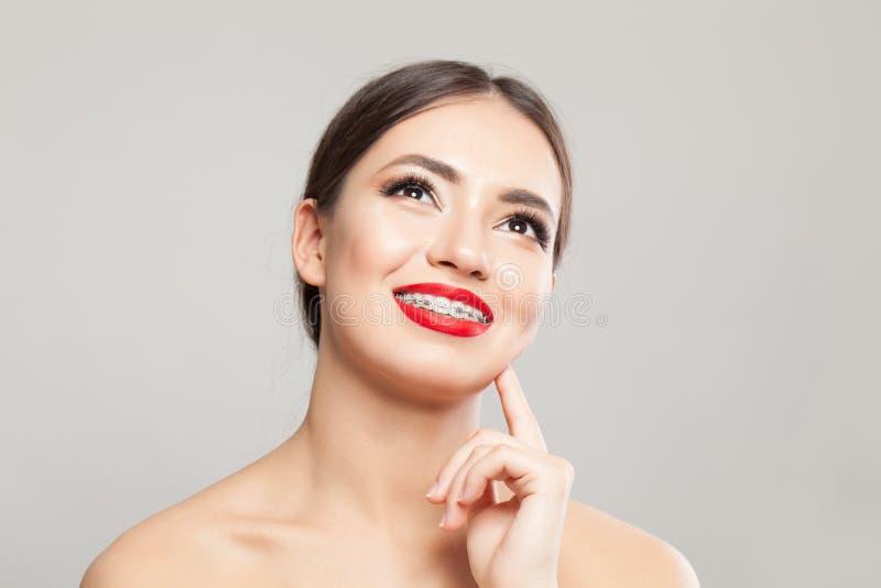 Gladlynt ung kvinna i hänglsenstående arkivfoto