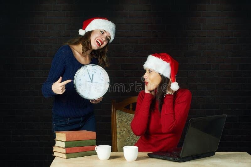 Gladlynt ung kvinna i hattar för jultomten` s arkivfoton