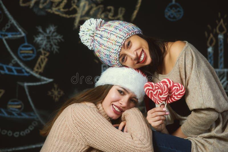 Gladlynt ung kvinna i hattar för jultomten` s fotografering för bildbyråer