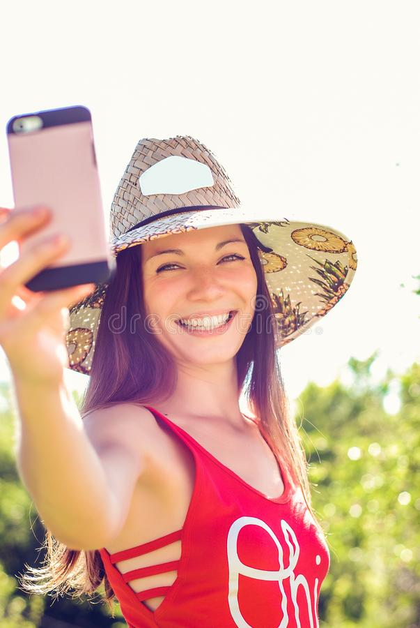 Gladlynt ung kvinna i hatten som tar selfie med mobiltelefonen på sommarsemesterort royaltyfria bilder