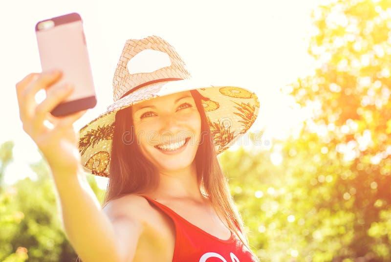 Gladlynt ung kvinna i hatten som tar selfie med mobiltelefonen på sommarsemesterort royaltyfri fotografi