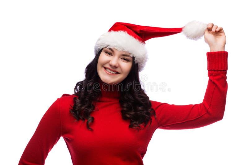 Gladlynt ung kvinna i rörande den isolerade julhatten för röd tröja royaltyfria bilder
