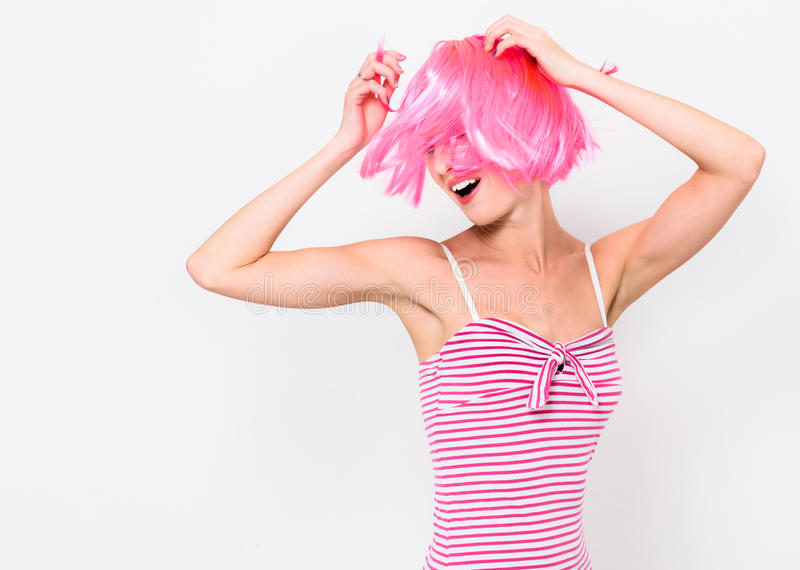 Gladlynt ung kvinna i rosa peruk och dans på vit bakgrund royaltyfria foton