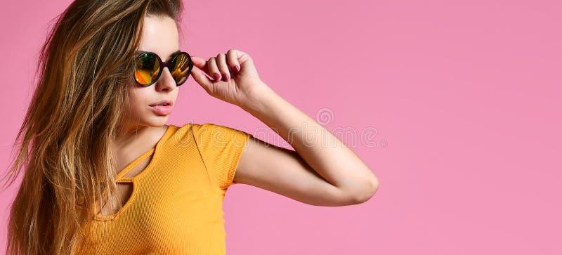 Gladlynt ung kvinna i solglasögon mot rosa bakgrund fotografering för bildbyråer