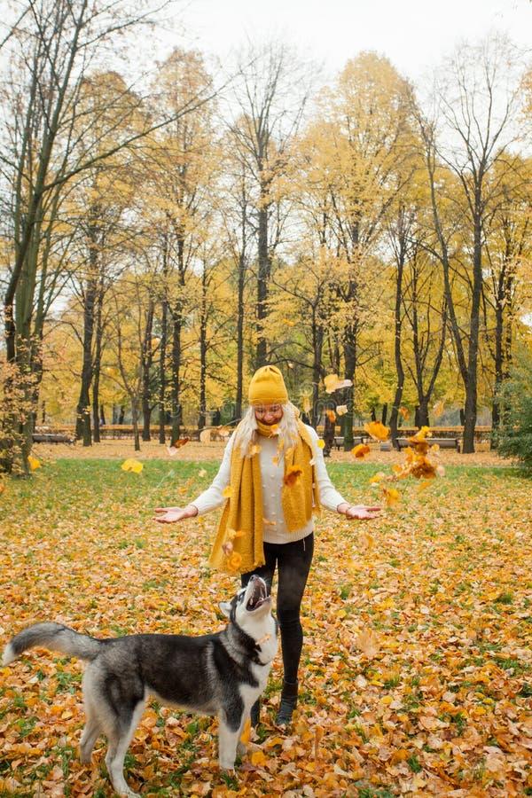 Gladlynt ung kvinna med gult skrovligt gå för hatt och för hund arkivbild