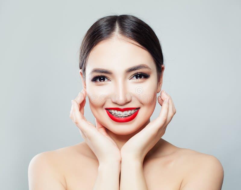 Gladlynt ung kvinna med hänglsen på tänder som skrattar och trycker på hennes framsida vid handen över vit bakgrund arkivfoto