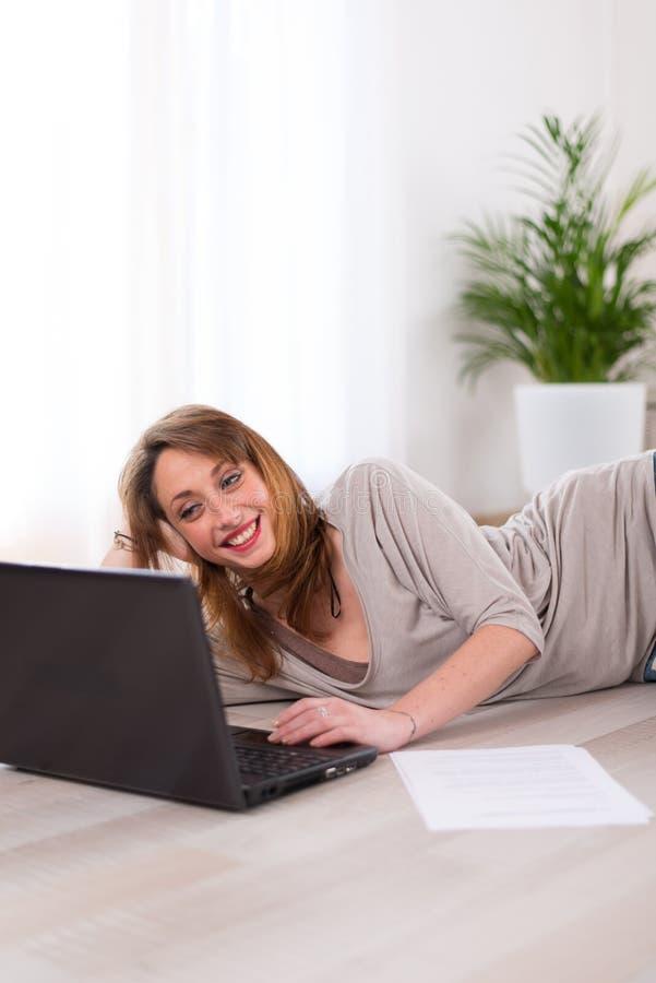 Gladlynt ung kvinna som är avkopplad hemma med bärbara datorn royaltyfria foton