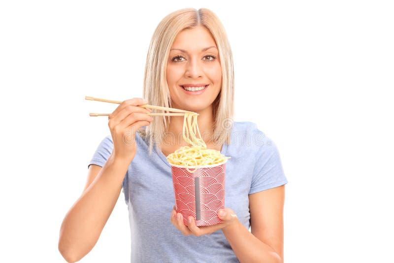 Gladlynt ung kvinna som äter nudlar arkivfoto
