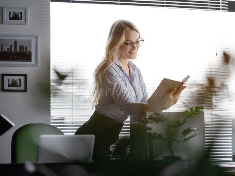 Gladlynt ung kvinna som får befordran och den nya arbetsplatsen royaltyfri bild