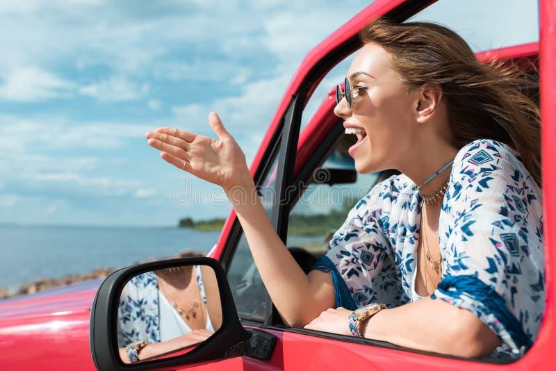gladlynt ung kvinna som gör en gest och talar i bil royaltyfria bilder