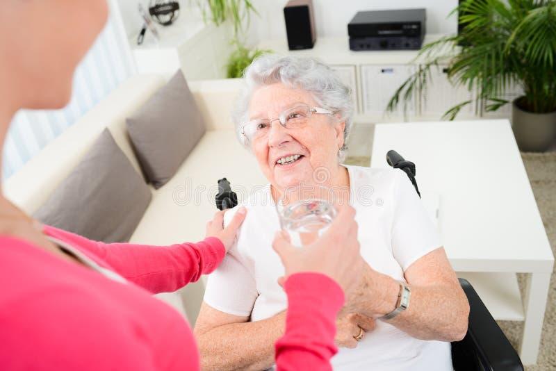 Gladlynt ung kvinna som hemma tar omsorg av en äldre kvinna på rullstolen royaltyfri fotografi