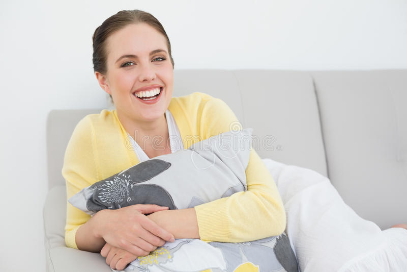 Gladlynt ung kvinna som kopplar av på soffan fotografering för bildbyråer