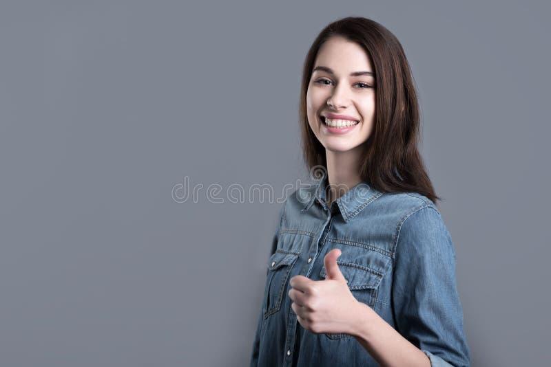 Download Gladlynt Ung Kvinna Som Ler Och Lyfter Tummen Arkivfoto - Bild av lycka, glädje: 78727770