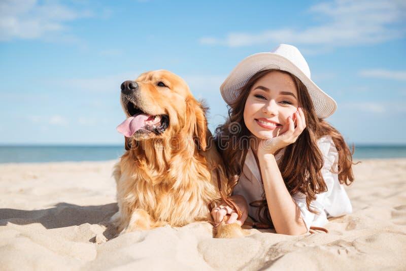 Gladlynt ung kvinna som ligger med hennes hund på stranden arkivbild
