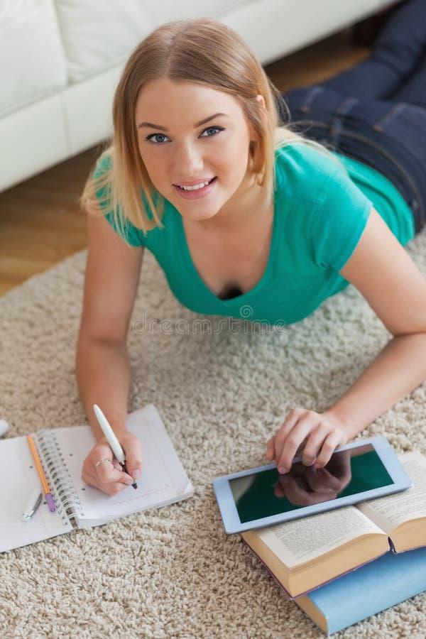 Gladlynt ung kvinna som ligger på golv genom att använda minnestavlan för att göra hennes assig arkivbild
