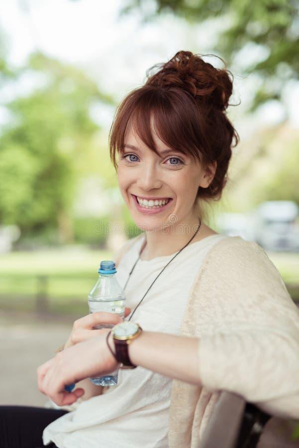 Gladlynt ung kvinna som rymmer en flaska av vatten royaltyfria bilder
