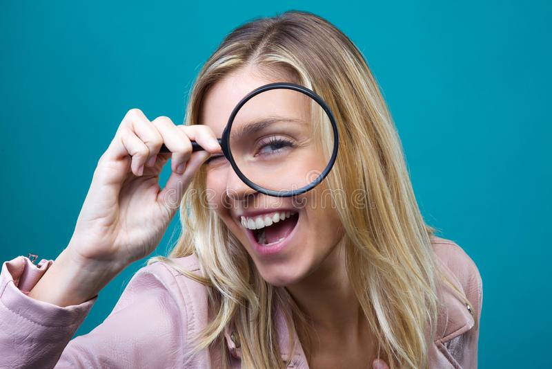 Gladlynt ung kvinna som ser till och med förstoringsglaset som isoleras över blå bakgrund arkivfoto