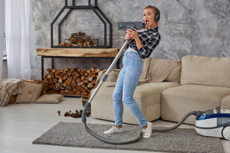 Gladlynt ung kvinna som tycker om sjunga solo med dammsugare, medan göra ren huset royaltyfri foto
