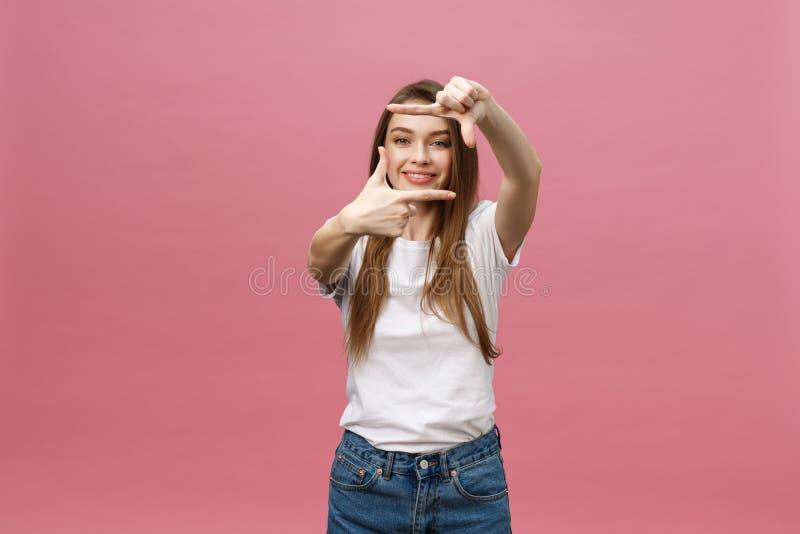 Gladlynt ung kvinna som vitt håller munnen öppen och att se förvånat och att göra den isolerade gesten för handfotoram på ljust royaltyfria foton