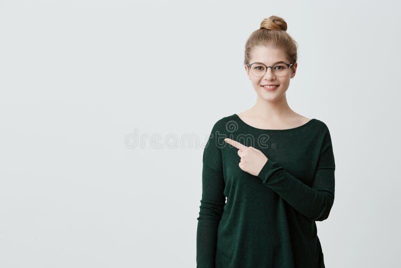 Gladlynt ung kvinnlig kund eller student med blont hår i tillfälligt grönt tröja och glasögon som i huvudsak ler royaltyfri bild