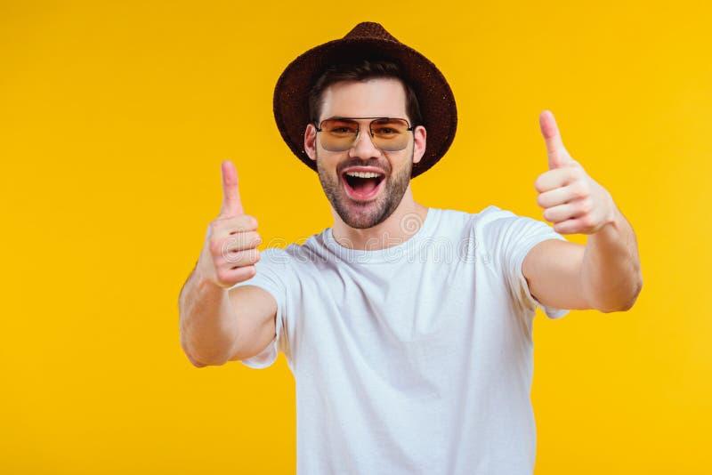 gladlynt ung man i den vita t-skjortan, hatten och solglasögon som visar upp tummar och ler på kameran royaltyfri fotografi