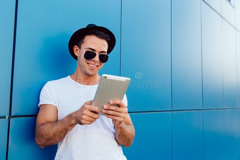 Gladlynt ung man som använder en minnestavladator, utomhus royaltyfria bilder