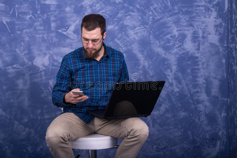 Gladlynt ung man som arbetar p? b?rbara datorn som placeras p? en stol som isoleras ?ver vit bakgrund Idérik freelancergrabb som  royaltyfria foton