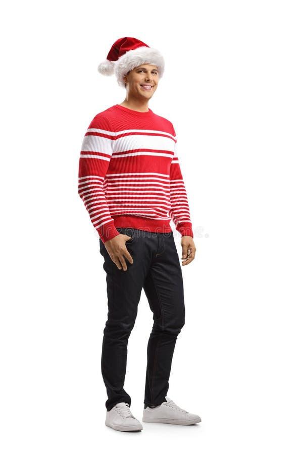 Gladlynt ung man som bär en julsanta hatt och en röd tröja fotografering för bildbyråer