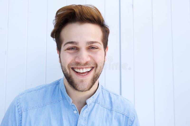 Gladlynt ung man som skrattar mot vit bakgrund arkivbild