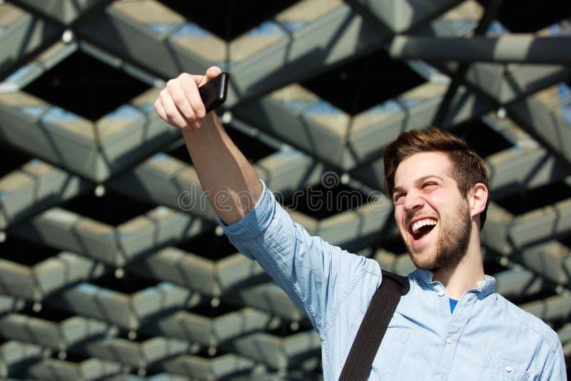 Gladlynt ung man som tar selfie royaltyfri bild