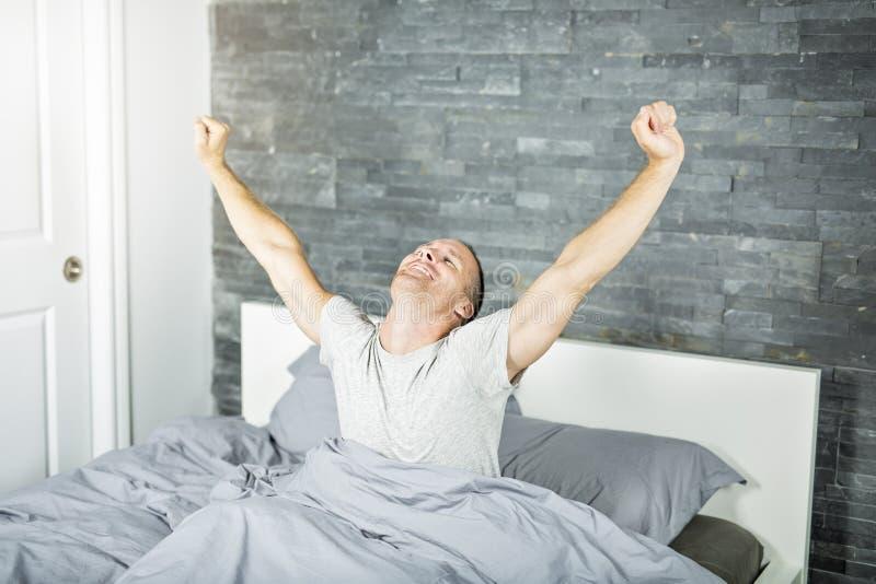 Gladlynt ung man som vaknar upp i säng och sträcker hans armar royaltyfria bilder