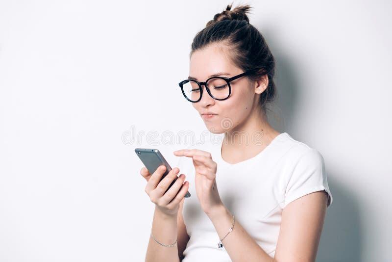 Gladlynt ung rödhårig mankvinnlig med gulligt leende, genom att använda mobiltelefonen som kontrollerar newsfeed på hennes social arkivbilder