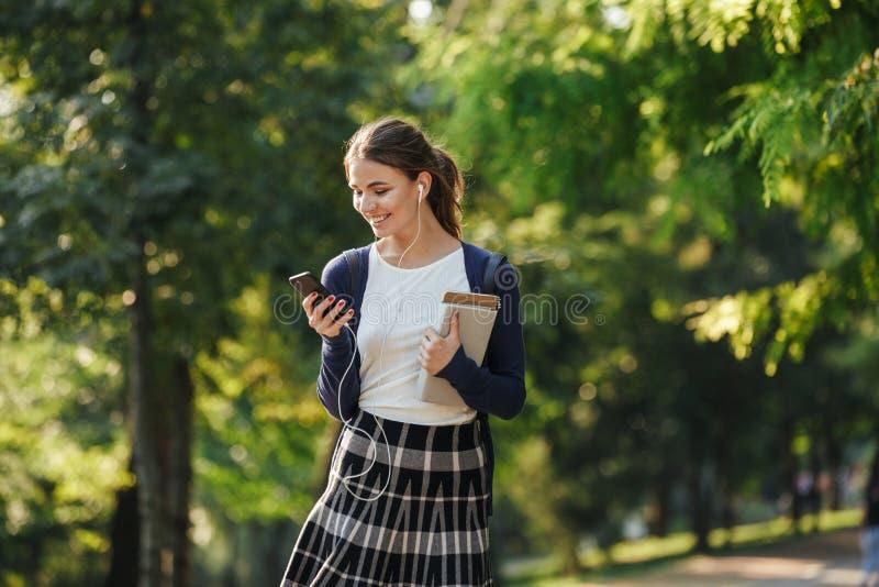 Gladlynt ung skolaflicka som utomhus går royaltyfri bild