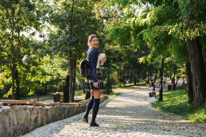 Gladlynt ung skolaflicka som utomhus går arkivfoton