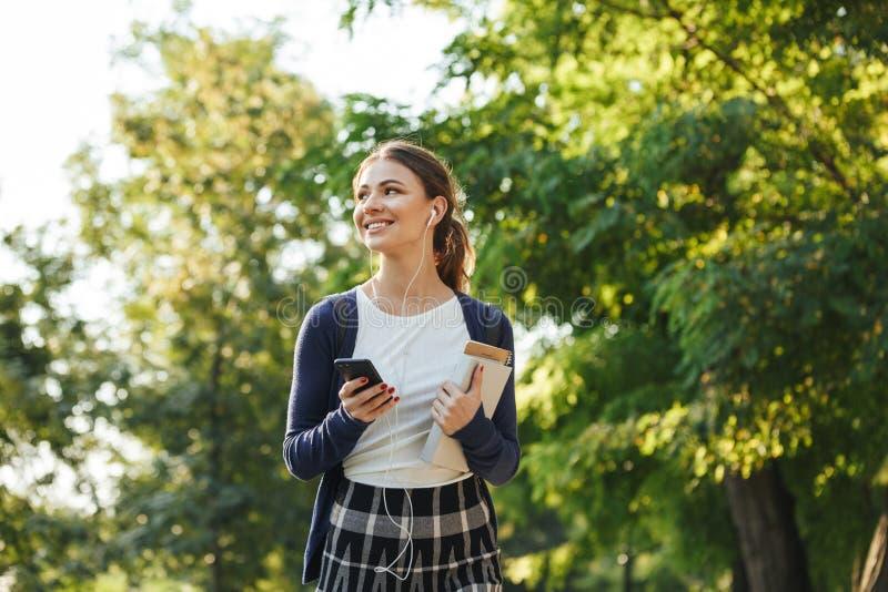 Gladlynt ung skolaflicka som utomhus går fotografering för bildbyråer