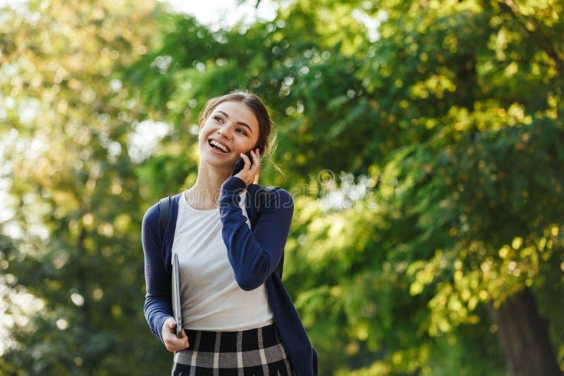 Gladlynt ung skolaflicka som utomhus går royaltyfria foton