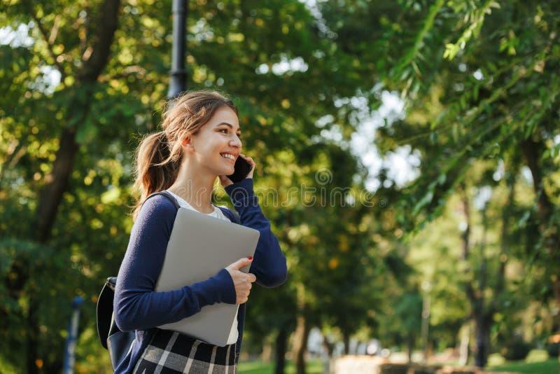 Gladlynt ung skolaflicka som utomhus går arkivfoto