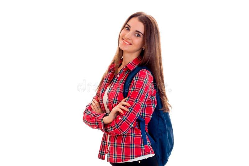 Gladlynt ung studentflicka med ryggsäcken som ser kameran och le som isoleras på vit bakgrund studentår arkivfoto