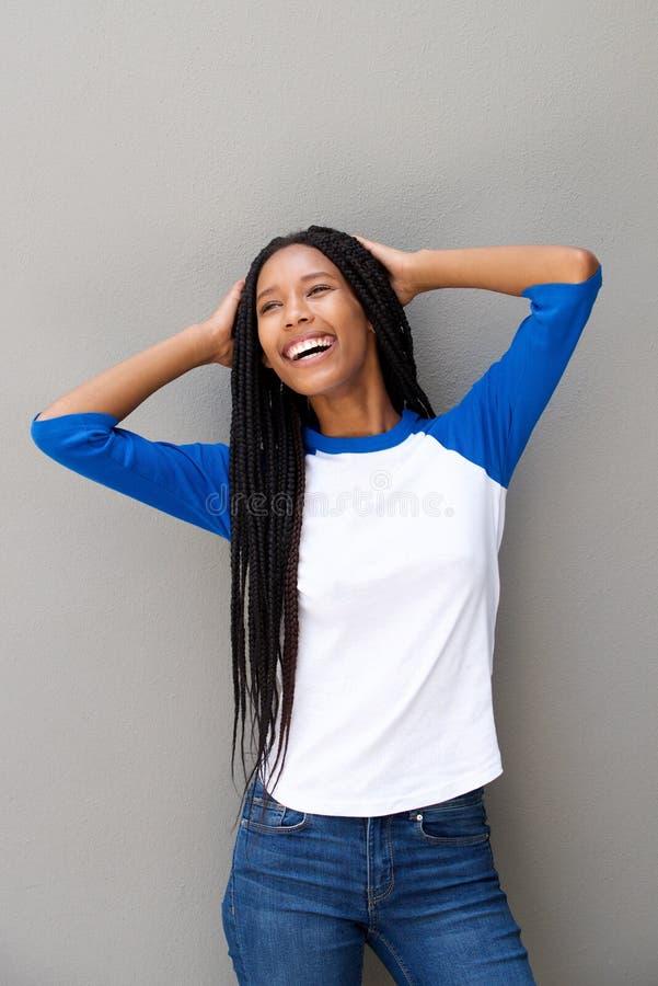 Gladlynt ung svart kvinna med flätat hår som ler mot den gråa väggen royaltyfria foton