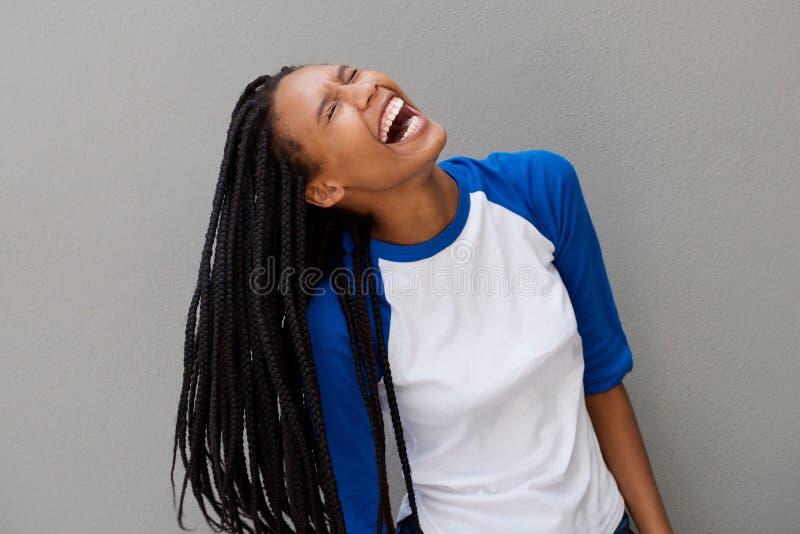 Gladlynt ung svart kvinna med långt flätat hår som skrattar på grå bakgrund royaltyfria bilder