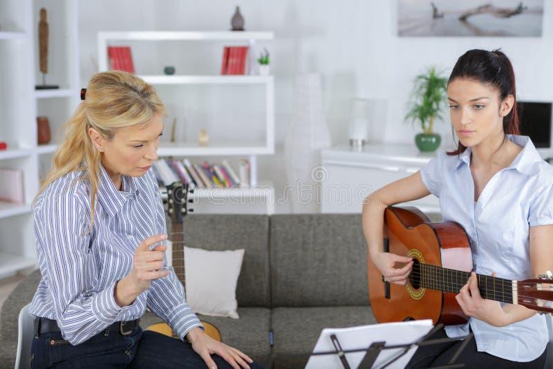Gladlynt ung tonårig musiker som spelar gitarren arkivfoto
